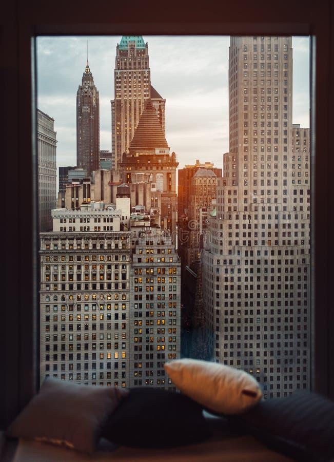 Άνετη στρωματοειδής φλέβα παραθύρων πολυτέλειας με την άποψη στους ουρανοξύστες πόλεων της Νέας Υόρκης στο χρόνο ηλιοβασιλέματος  στοκ εικόνες