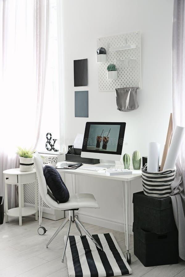 Άνετος εργασιακός χώρος με τον υπολογιστή στο γραφείο στο σπίτι στοκ εικόνα με δικαίωμα ελεύθερης χρήσης