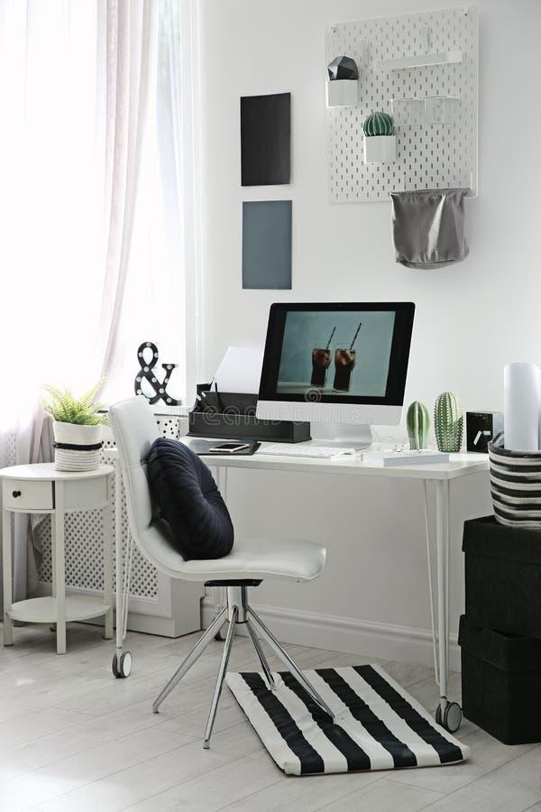 Άνετος εργασιακός χώρος με τον υπολογιστή στο γραφείο στο σπίτι στοκ εικόνα
