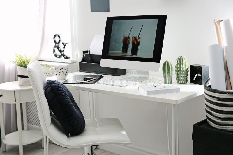 Άνετος εργασιακός χώρος με τον υπολογιστή στο γραφείο στοκ εικόνα με δικαίωμα ελεύθερης χρήσης