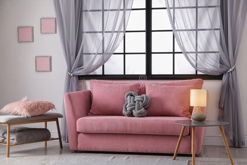 Άνετος καναπές κοντά στο παράθυρο στο σύγχρονο καθιστικό στοκ φωτογραφία