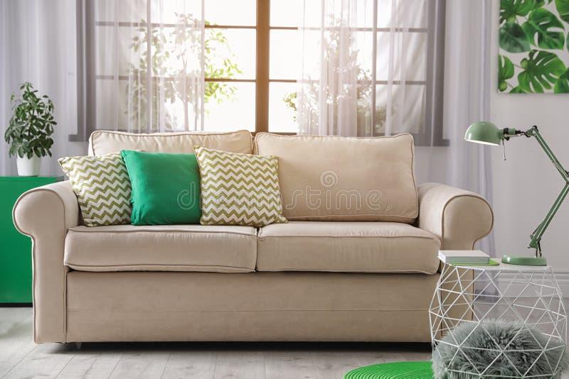 Άνετος καναπές κοντά στο παράθυρο στο σύγχρονο καθιστικό στοκ εικόνες με δικαίωμα ελεύθερης χρήσης