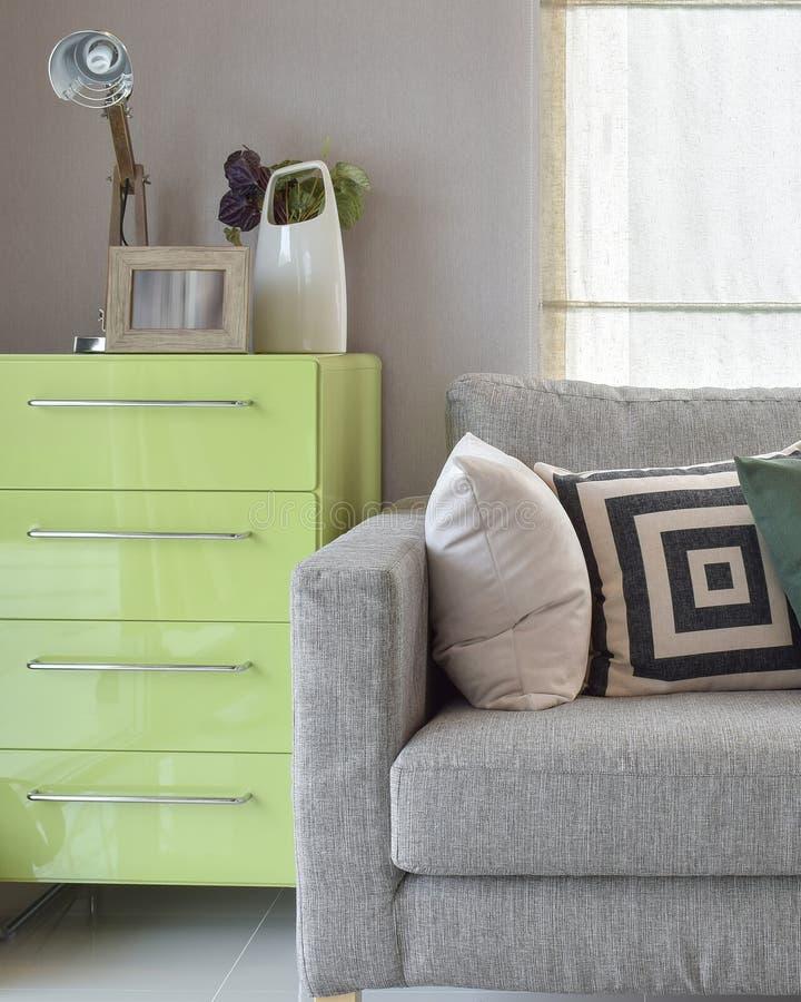 Άνετος καναπές με τα γεωμετρικά μαξιλάρια σχεδίων και τον πράσινο μπουφέ μέσα στοκ φωτογραφίες
