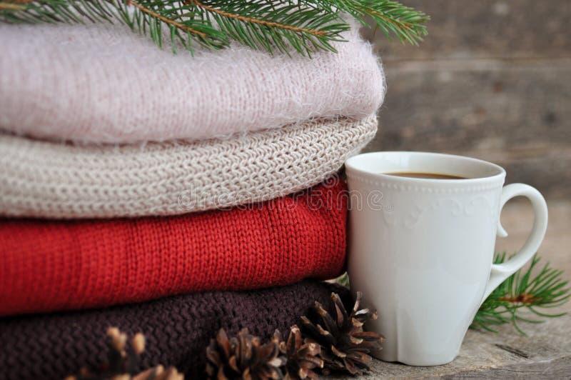 Άνετος χειμώνας: πλεκτοί ενδύματα, ερυθρελάτες, κώνοι και φλυτζάνι του cofe σε ένα παλαιό ξύλινο υπόβαθρο στοκ φωτογραφίες με δικαίωμα ελεύθερης χρήσης
