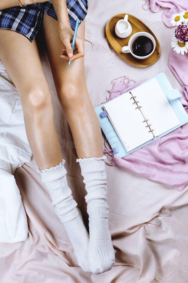 Άνετος flatlay με τη λευκιά μαυρισμένη γυναίκα στις άσπρες κάλτσες που κάθεται στο χ στοκ φωτογραφίες