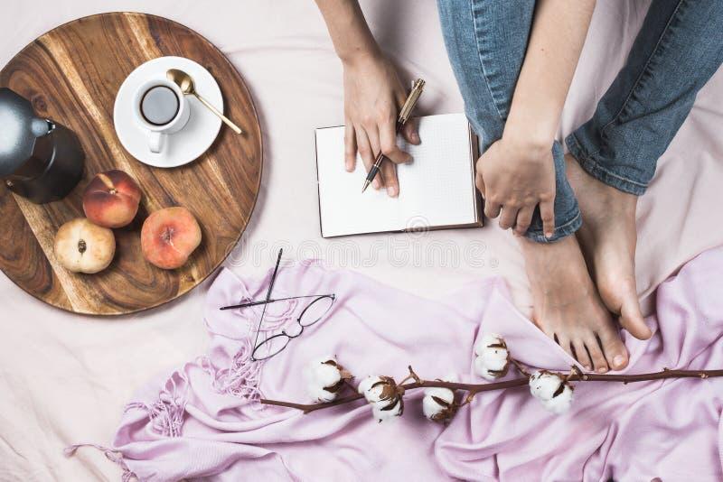 Άνετος flatlay των ποδιών γυναικών στα τζιν στο κρεβάτι της με το φλυτζάνι του coffe στοκ φωτογραφίες