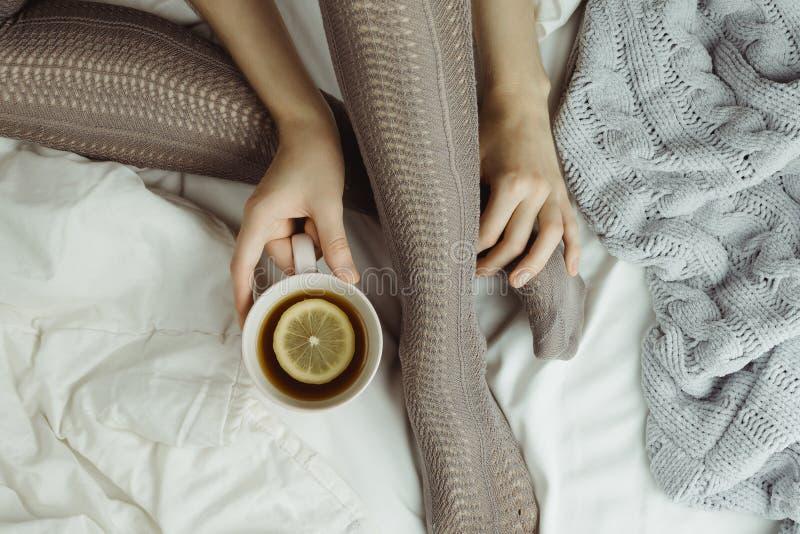 Άνετος flatlay των ποδιών γυναικών ` s στις θερμές γκρίζες γυναικείες κάλτσες στο κρεβάτι με το πλεκτά πουλόβερ και το κάλυμμα κα στοκ εικόνες