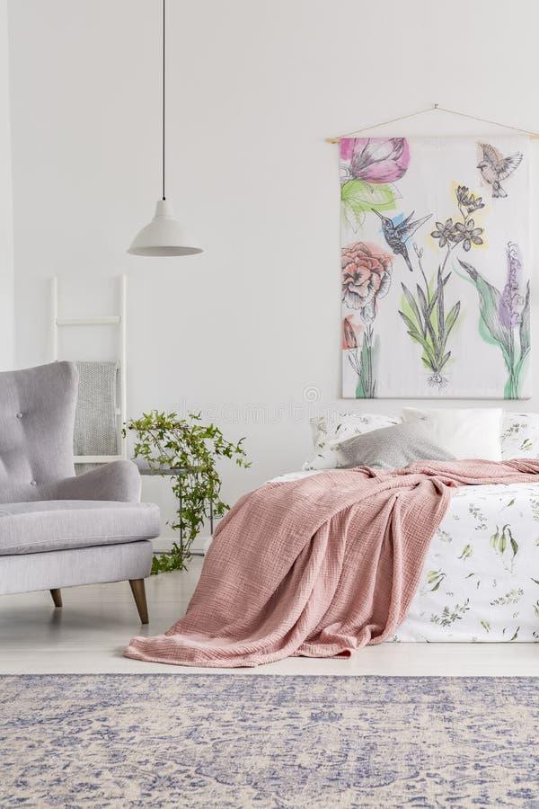 Άνετο εσωτερικό κρεβατοκάμαρων με ένα κρεβάτι που ντύνεται στα άσπρα και πράσινα φύλλα και το κάλυμμα ροδάκινων στοκ φωτογραφία με δικαίωμα ελεύθερης χρήσης
