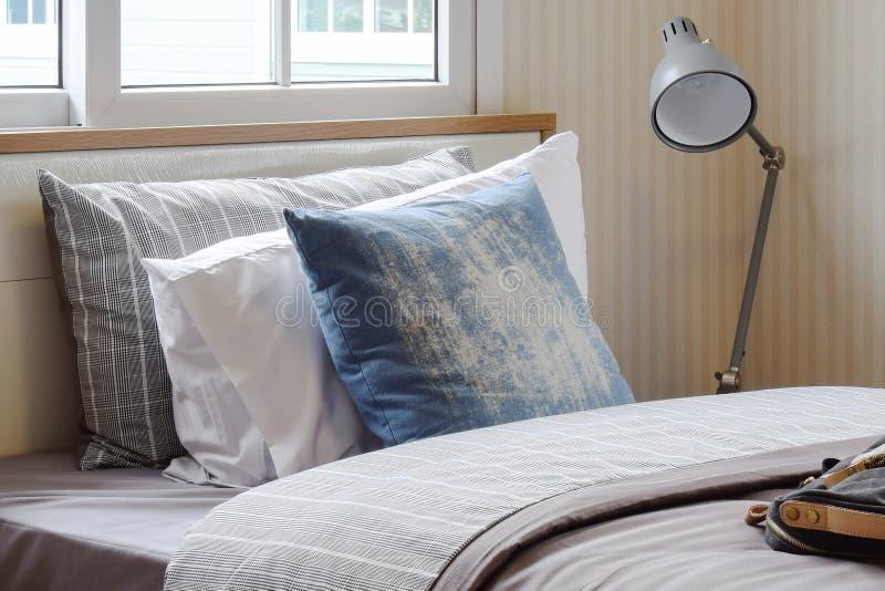 Άνετο εσωτερικό κρεβατοκάμαρων με τα μαξιλάρια και το λαμπτήρα ανάγνωσης στον πίνακα πλευρών στο σπίτι στοκ φωτογραφίες
