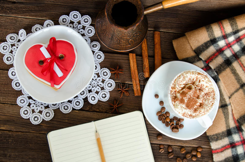 Άνετο υπόλοιπο Cappuccino, διαμορφωμένο καρδιά κέικ, ένα σημειωματάριο με ένα μολύβι, δοχεία του καφέ στοκ εικόνες