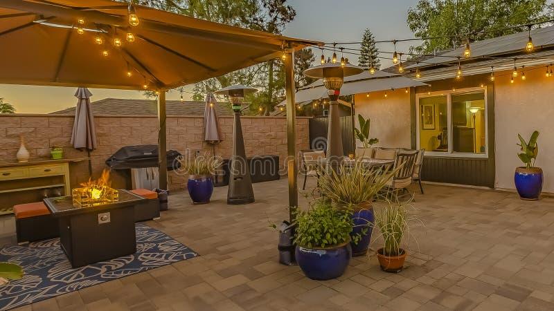 Άνετο patio πετρών πλαισίων πανοράματος με τη σειρά των φω'των πέρα από μια καλυμμένη να καθίσει και να δειπνήσει περιοχή στοκ φωτογραφίες