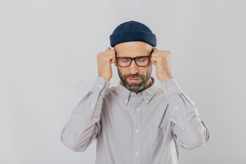 Άνθρωποι, έννοια έντασης και ημικρανίας Το καταθλιπτικό αξύριστο νέο αρσενικό πάσχει από τον πονοκέφαλο, κρατά παραδίδει τις πυγμ στοκ εικόνα