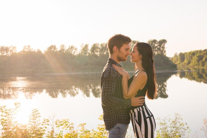 Άνθρωποι, έννοια αγάπης και φύσης - πορτρέτο του νέου όμορφου ζεύγους που αγκαλιάζει το ένα το άλλο στεμένος πέρα από τη φύση στοκ εικόνες