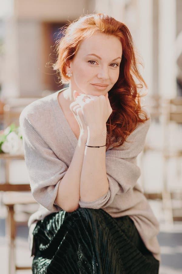 Άνθρωποι, έννοια ελεύθερου χρόνου Το ευτυχές καλό θηλυκό με την πανούργη τρίχα, κρατά τα χέρια μαζί κάτω από το πηγούνι, που ντύν στοκ εικόνες