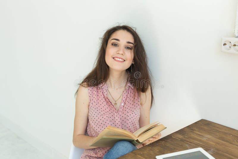 Άνθρωποι, βιβλία και έννοια εκπαίδευσης - πορτρέτο της ευτυχούς συνεδρίασης γυναικών σπουδαστών με ένα βιβλίο στοκ εικόνες