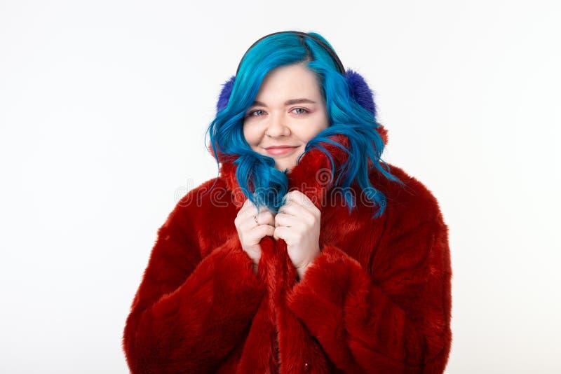 Άνθρωποι, ζώα προστασίας και έννοια μόδας - το όμορφο κορίτσι με την μπλε τρίχα έντυσε στο κόκκινο θερμό σακάκι σε τεχνητό στοκ εικόνα με δικαίωμα ελεύθερης χρήσης