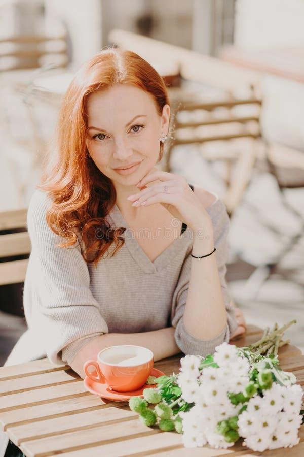 Άνθρωποι και έννοια τρόπου ζωής Το κοκκινομάλλες θηλυκό έχει παρακαλέσει την έκφραση, πίνει τον καφέ, θέτει στην καφετέρια με τα  στοκ εικόνα με δικαίωμα ελεύθερης χρήσης