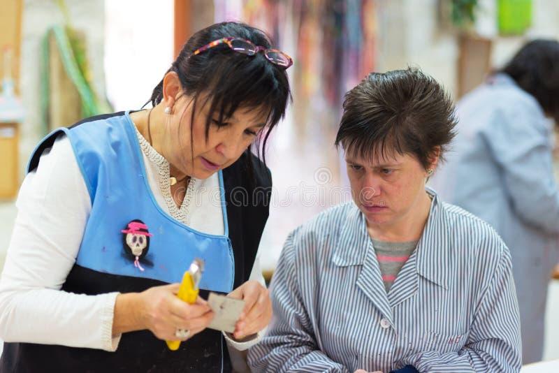 Άνθρωποι με ειδικές ανάγκες ή ειδικές ανάγκες που συνεργάζονται με τους δασκάλους τους στο εργαστήριο της επαγγελματικής θεραπεία στοκ εικόνες