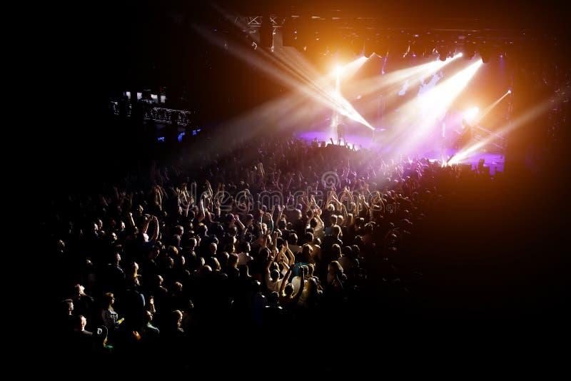 Άνθρωποι με τα χέρια τους επάνω σε μια συναυλία της αγαπημένης ομάδας τους στοκ εικόνες
