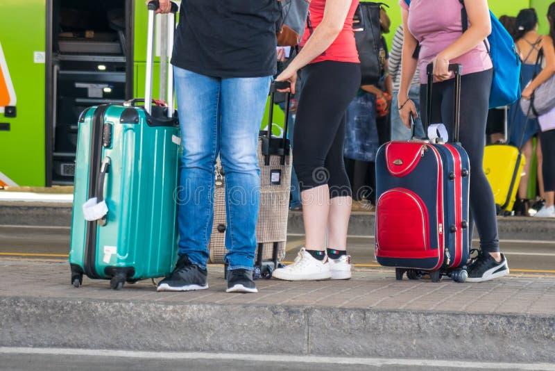 Άνθρωποι με τις βαλίτσες στη στάση λεωφορείου στοκ εικόνες