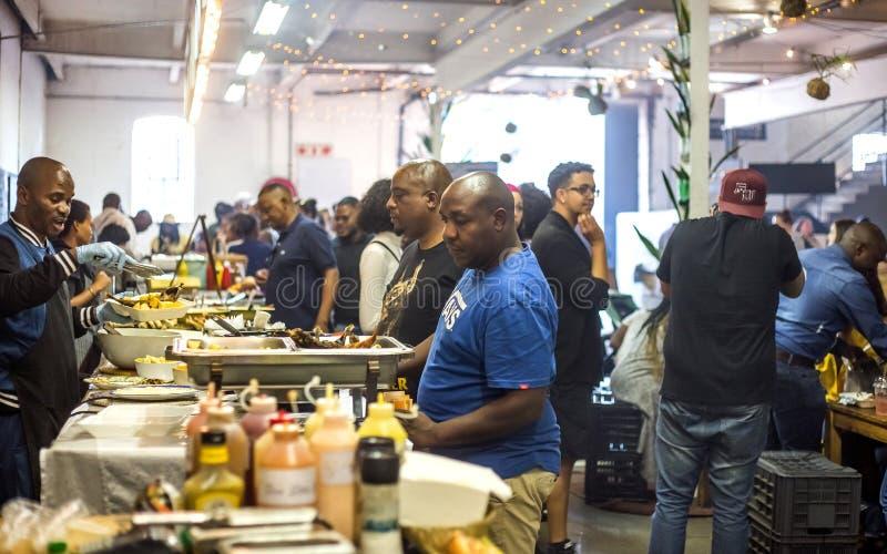 Άνθρωποι που αγοράζουν τα τρόφιμα σε μια αγορά τροφίμων στοκ εικόνα με δικαίωμα ελεύθερης χρήσης