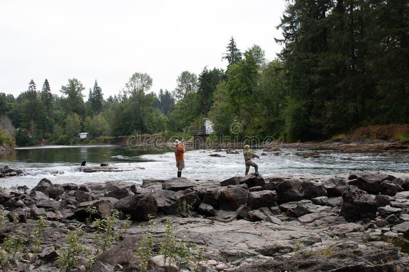 Άνθρωποι που αλιεύουν στην όχθη ποταμού στοκ εικόνα με δικαίωμα ελεύθερης χρήσης