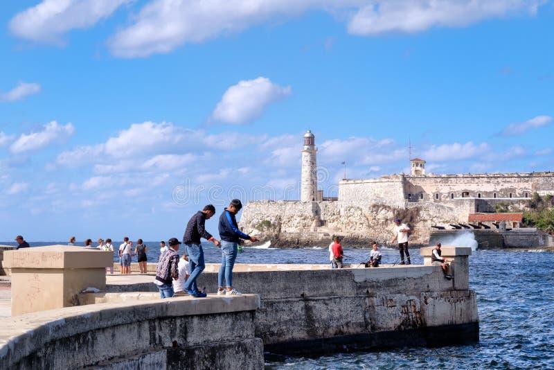 Άνθρωποι που αλιεύουν στο malecon seawall στην Αβάνα με το φρούριο EL Morro στο υπόβαθρο στοκ εικόνες με δικαίωμα ελεύθερης χρήσης