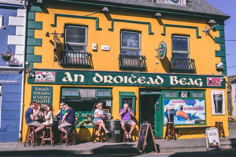 Άνθρωποι που απολαμβάνουν μια ηλιόλουστη ημέρα στα μπαρ Dingle, μικρή πόλη λιμένων σημείο Dingle της Ιρλανδίας της χερσονήσου στοκ εικόνες