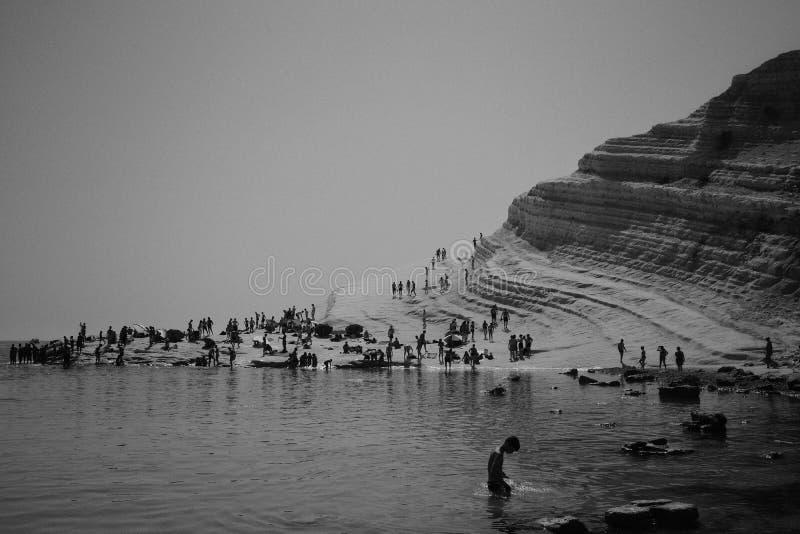 Άνθρωποι που απολαμβάνουν μια ημέρα σε μια παραλία κοντά σε έναν δύσκολο λόφο στοκ φωτογραφία με δικαίωμα ελεύθερης χρήσης