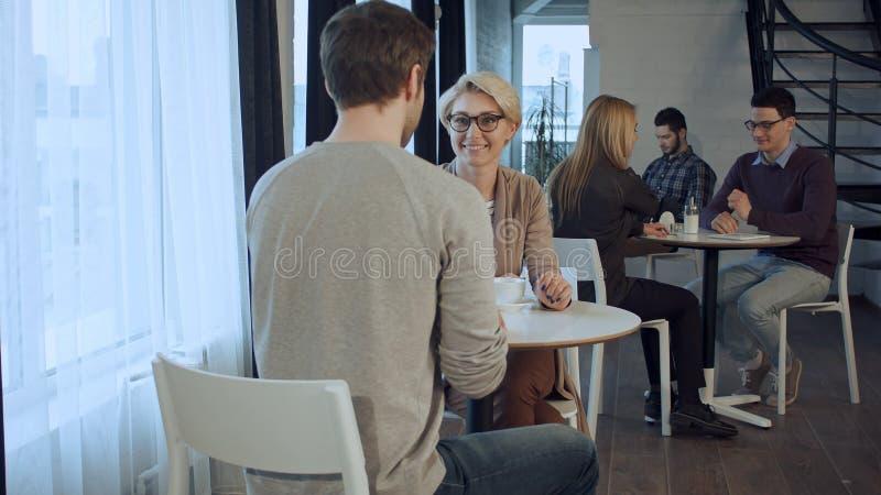 Άνθρωποι που απολαμβάνουν τον καφέ, που εργάζονται και που επικοινωνούν στον καφέ το πρωί στοκ φωτογραφίες