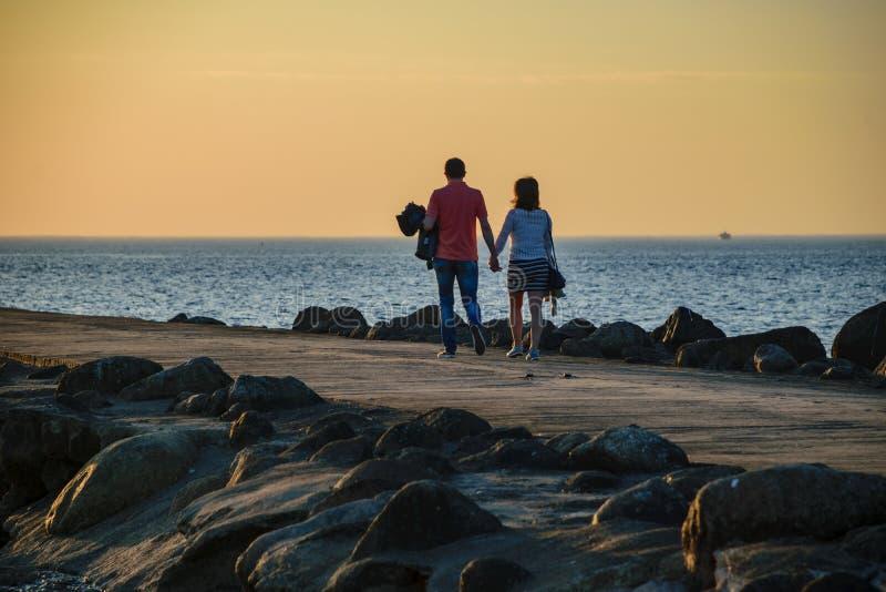 άνθρωποι που απολαμβάνουν το ηλιοβασίλεμα στο brakewater στη θάλασσα στοκ εικόνες
