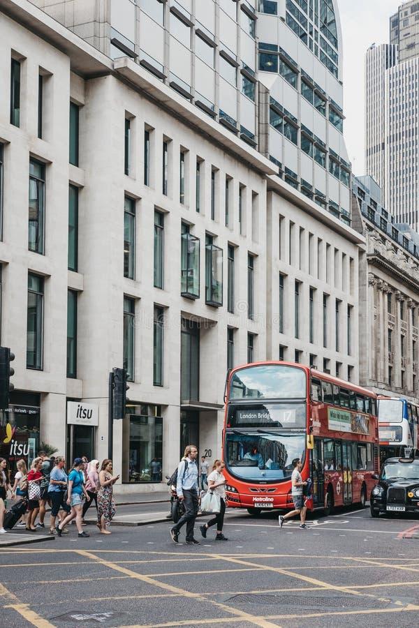 Άνθρωποι που διασχίζουν το δρόμο σε ένα για τους πεζούς πέρασμα μπροστά από το κόκκινο λεωφορείο στην πόλη του Λονδίνου, UK στοκ εικόνες