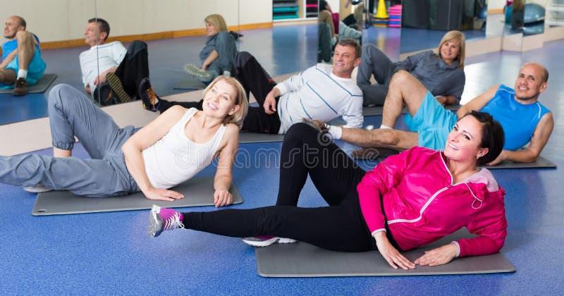 Άνθρωποι που εκπαιδεύουν σε μια γυμναστική στα αθλητικά χαλιά στοκ εικόνες