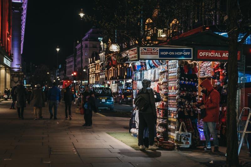 Άνθρωποι που εξετάζουν τα αναμνηστικά σε μια στάση τουριστών στην οδό της Οξφόρδης, Λονδίνο, UK, το βράδυ στοκ εικόνα