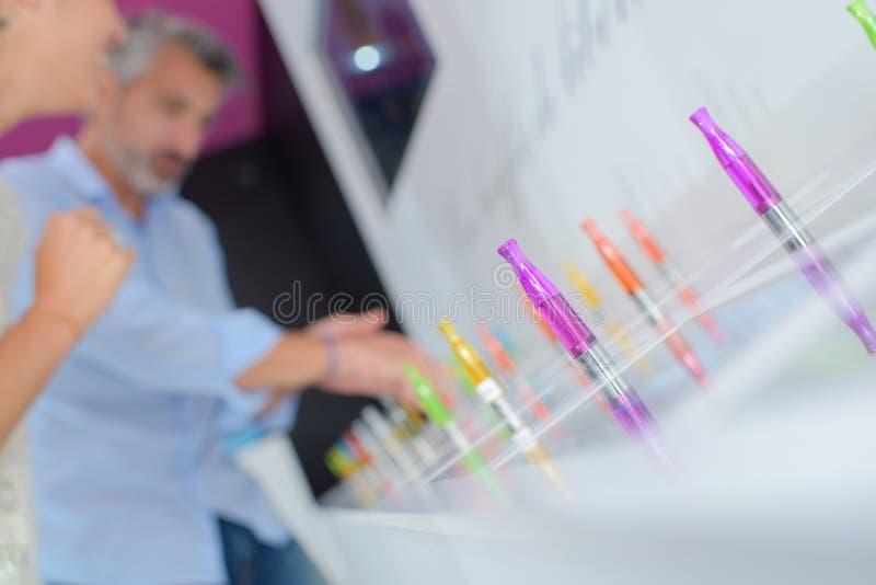 Άνθρωποι που εξετάζουν τα ζωηρόχρωμα ηλεκτρονικά τσιγάρα στοκ φωτογραφία