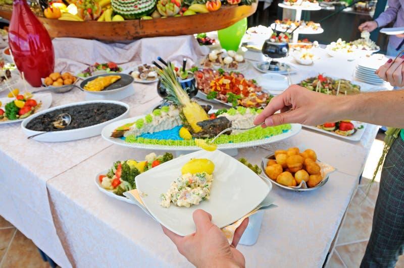 Άνθρωποι που εξυπηρετούν τα τρόφιμα μπουφέδων υπαίθρια στοκ εικόνες με δικαίωμα ελεύθερης χρήσης