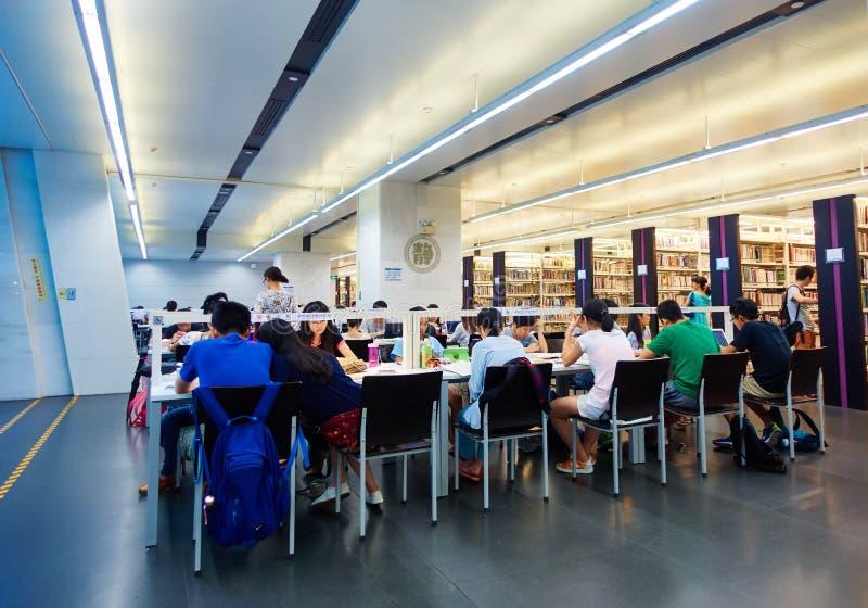 Άνθρωποι που διαβάζουν τα βιβλία στην αίθουσα βιβλιοθηκών στοκ εικόνες