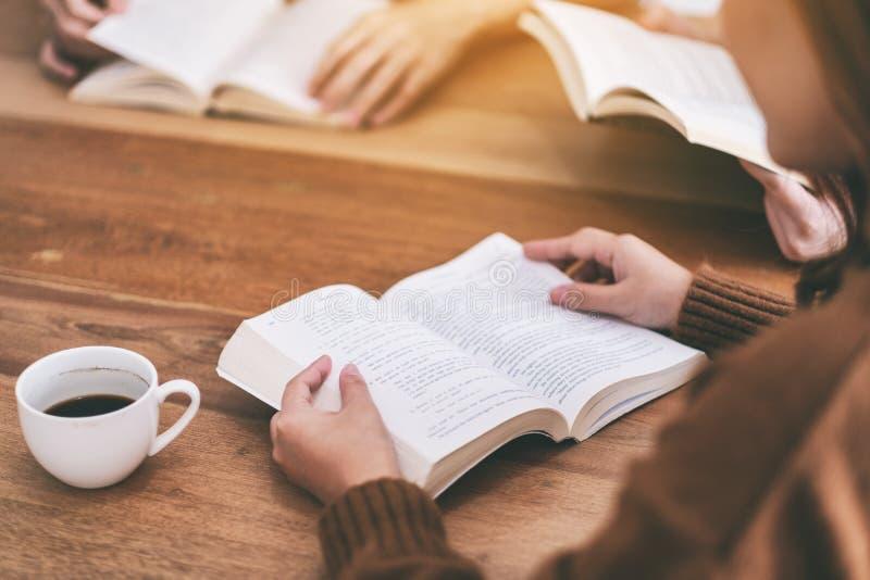 Άνθρωποι που κάθονται και που απολαμβάνουν τα βιβλία μαζί στον ξύλινο πίνακα στοκ φωτογραφίες με δικαίωμα ελεύθερης χρήσης