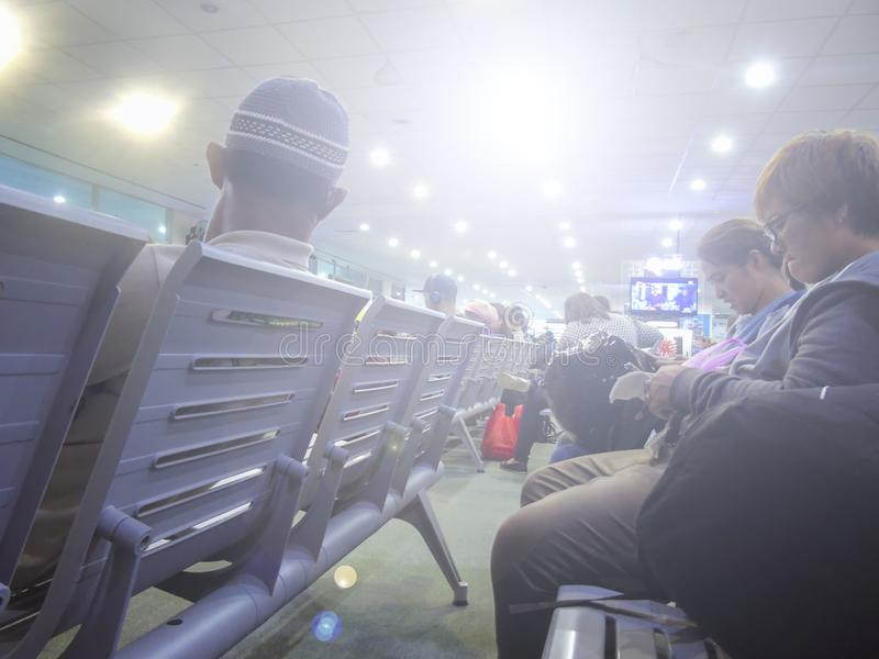 Άνθρωποι που κάθονται στον πάγκο που περιμένει τις πτήσεις τους στον αερολιμένα στοκ φωτογραφία