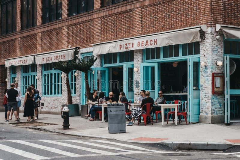 Άνθρωποι που κάθονται στους υπαίθριους πίνακες του εστιατορίου ι παραλιών πιτσών στοκ φωτογραφίες