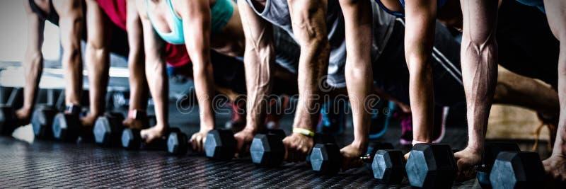 Άνθρωποι που κάνουν την ώθηση UPS με τον αλτήρα στη γυμναστική στοκ φωτογραφίες