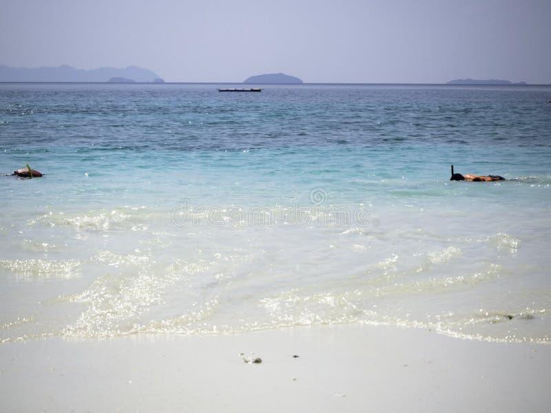 Άνθρωποι που κολυμπούν με αναπνευτήρα σε μια τυρκουάζ τροπική θάλασσα από ένα άσπρο αμμώδες β στοκ εικόνες