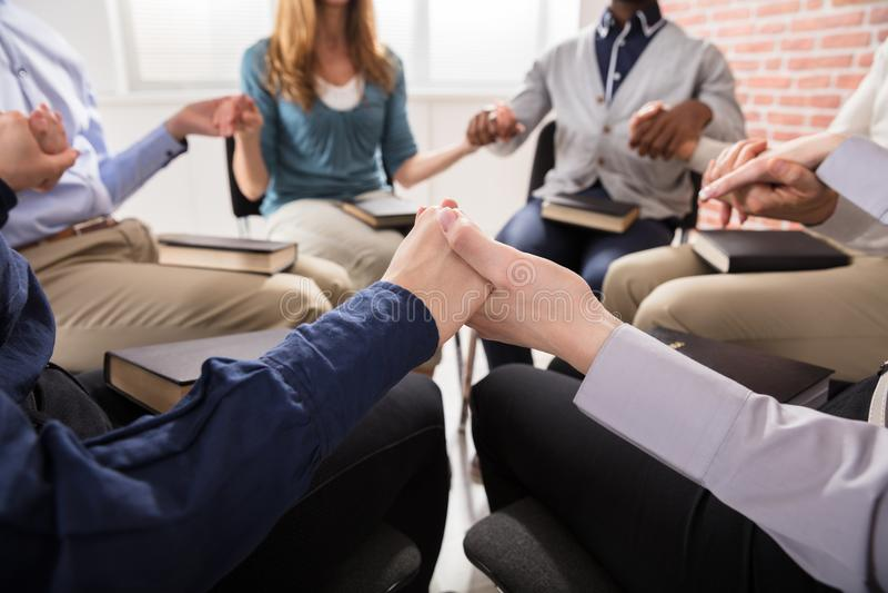 Άνθρωποι που κρατούν κάθε άλλοι χέρι που προσεύχεται από κοινού στοκ φωτογραφία