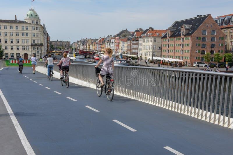 Άνθρωποι που οδηγούν τα ποδήλατα στη γέφυρα στο κέντρο της Κοπεγχάγης, Δανία στοκ φωτογραφία