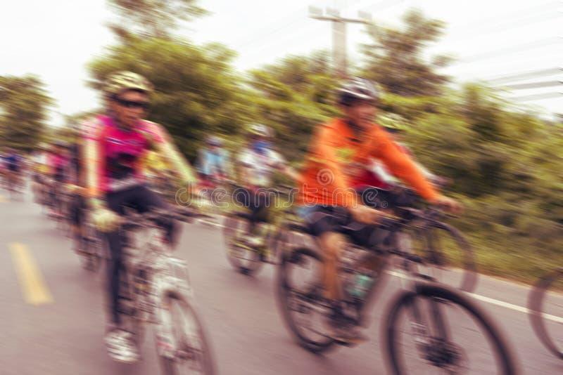 Άνθρωποι που οδηγούν τα ποδήλατα με τη θαμπάδα κινήσεων στοκ εικόνες