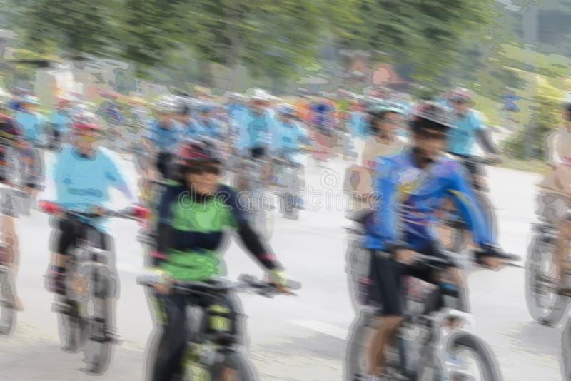 Άνθρωποι που οδηγούν τα ποδήλατα με τη θαμπάδα κινήσεων στοκ φωτογραφία