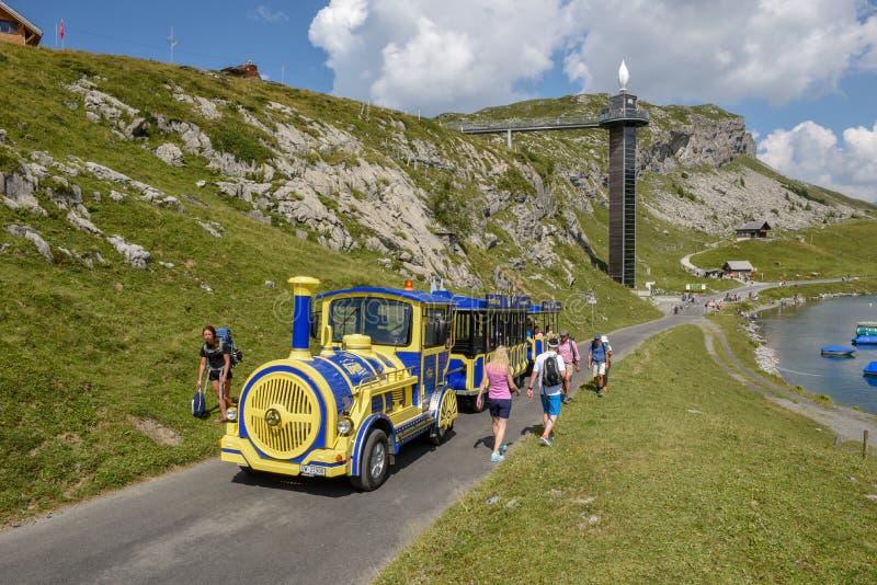 Άνθρωποι που περπατούν και που ταξιδεύουν σε ένα τραίνο τουριστών σε melchsee-Fru στοκ φωτογραφία με δικαίωμα ελεύθερης χρήσης