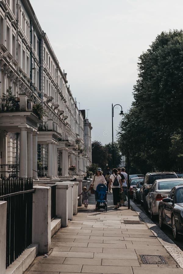 Άνθρωποι που περπατούν μετά από τα terraced σπίτια στο Νότινγκ Χιλ, Λονδίνο, UK στοκ εικόνα