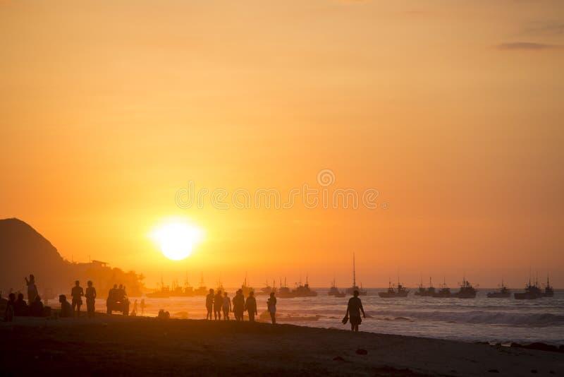 Άνθρωποι που περπατούν στην παραλία Mancora κατά τη διάρκεια του πορτοκαλιού ηλιοβασιλέματος στοκ εικόνα