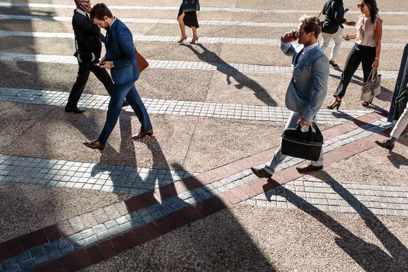 Άνθρωποι που περπατούν στο γραφείο το πρωί σε έναν δρόμο με έντονη κίνηση στοκ εικόνα με δικαίωμα ελεύθερης χρήσης